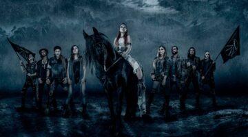 Banda Eluveitie posa para foto. Figura central é uma menina de branco montada em cavalo.