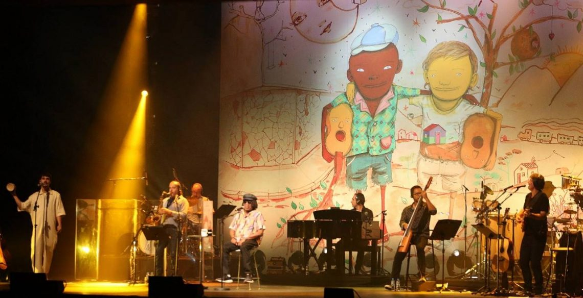Cantor Milton Nascimento no palco com toda sua banda. Ao fundo uma imagem que faz referência ao album Clube da Esquina, um desenho dele com Lô Borges abraçados.