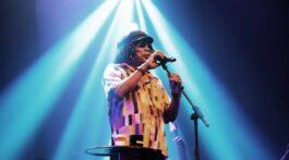 Milton Nascimento cantando com luz de refletor vindo de cima para baixo.