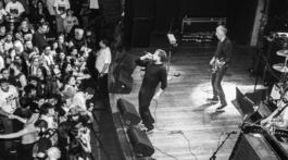 Banda Black Flag tocando para plateia cheia em foto preto e branca