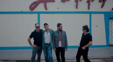 """banda barão vermelho posa para foto em frente a parede escrito """"happy"""""""