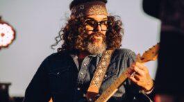 Guitarra brant bjork toca sua guitarra na frente de céu azul e ao ar livre