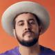 Rodrigo Suricato posa para foto em fundo vermelho