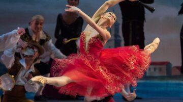 Bailarina Oksana Bondareva de vestido vermelho se apresenta
