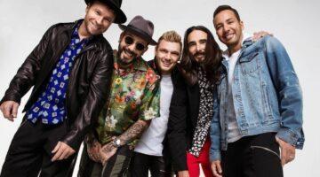 Banda Backstreet Boys posa para foto em fundo branco e com roupas coloridas, rindo e se abraçando