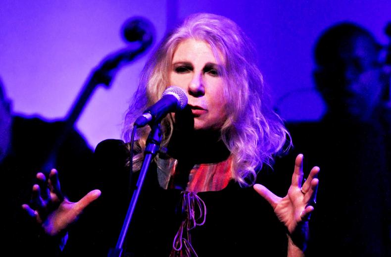 Cantora Annie, da banda Renaissance, se apresenta com fundo purpura