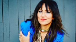 A cantora KT Tunstall sorri para foto de camisa azul e fundo cinza