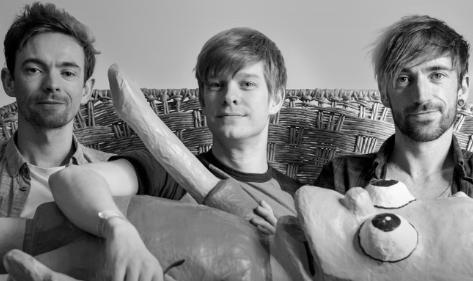 Banda TTNG posa para foto em preto e branco segurando boneco gigante