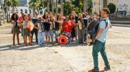 Orquestra Sanfônica ri para fotografia em dia ensolarado