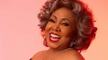 Alcione ri para foto em fundo rosa e bem iluminado