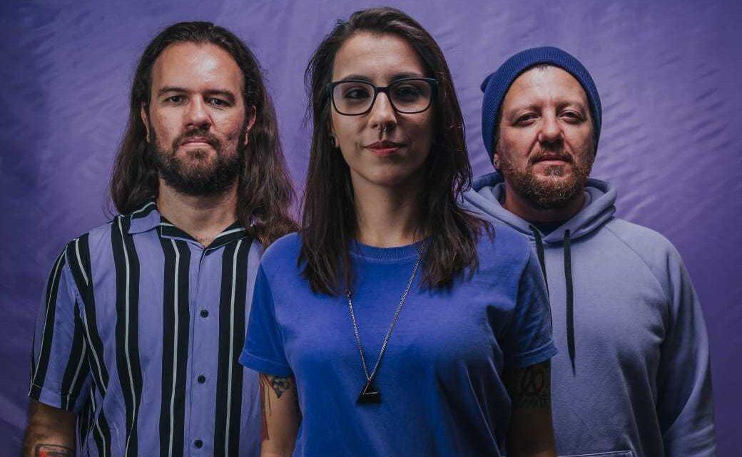 Banda Teorias do Amor Moderno posa para foto em fundo púrpura
