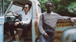 Black Pumas tira foto em carro velho e degradado com aspecto vintage