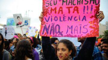 Menina segura uma faixa com dizeres contra o feminicidio